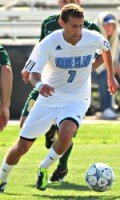 URI men's soccer player dribbling