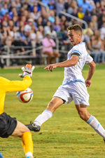 URI men's soccer player shooting on goalie