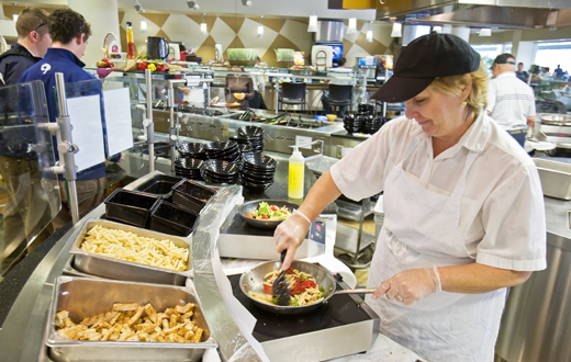 cafeteria worker preparing pasta dish
