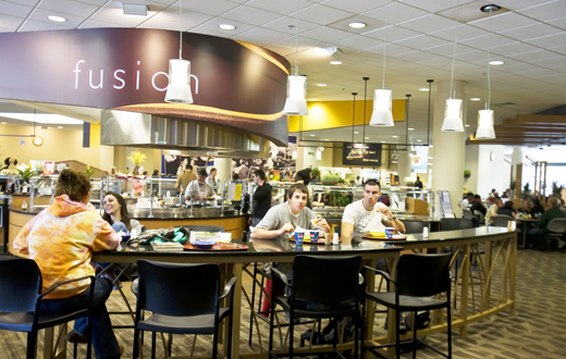 students eating at bar-style table in cafeteria
