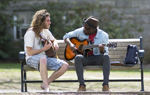 two students playing guitar on a bench