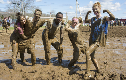 students posing covered in mud at ouzeball