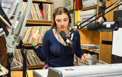 student at a microphone doing a radio show