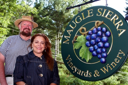 From left husband and wife Paul and Betty Maugle, co-owners of Maugle Sierra Vineyards in Ledyard, stand next to a large hand-crafted sign situated at the entrance of the vineyard. Photo by Cheryl Albaine