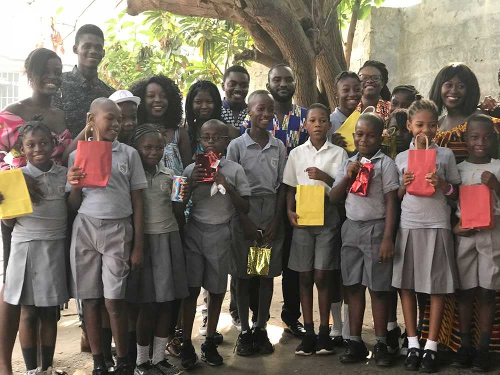 Tejan-Jalloh (third from left) and her peers donating dental kits to children at a primary school in Sierra Leone.