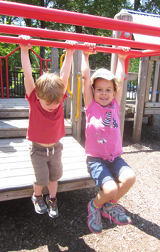 two children hanging on the CDC playground
