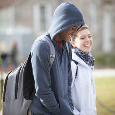 two students walking on campus smiling