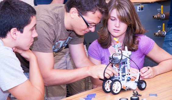 teacher working with students on a mechanical device