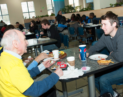 student talking with older adult in cafeteria