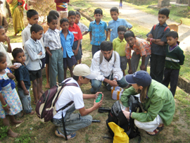 URI students with Indian people doing water testing in India