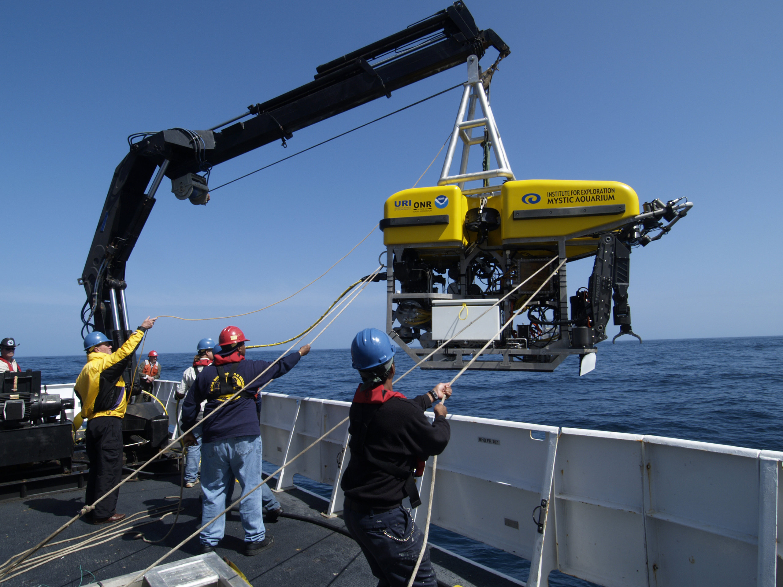 "Dr. Robert Ballard (in yellow jacket) launches ""Hercules,"" a remotely operated vehicle, over the side of the NOAA research vessel ""Ronald H. Brown"" on 5/30. He has reached the site of the Titanic shipwreck and will begin photographing and mapping the site with this ROV by nightfall."