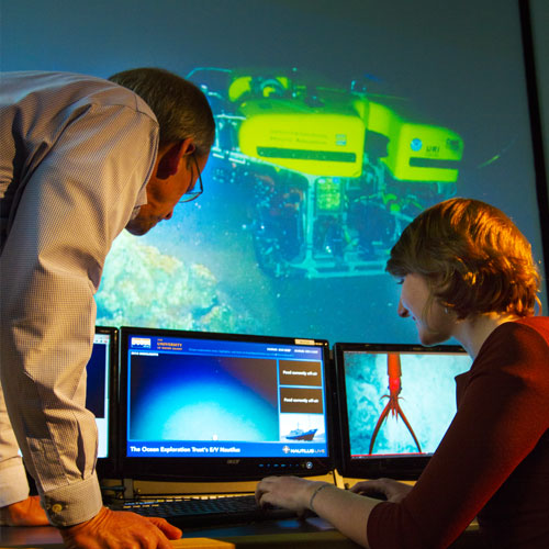 Professor Steven Carey and a student check a feed from E/V Nautilus in GSO's Inner Space Center.