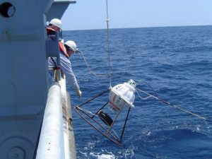 Scientists deploy a Model 6.2 Inverted Echo Sounder, produced by GSO/URI. Photo credit: Dynamics of Ocean Currents and Fronts Lab.