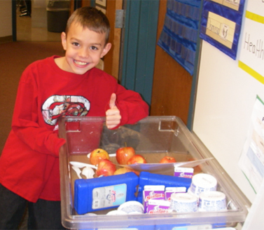child smiling next to healthy foods