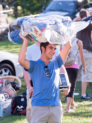 student carrying clothing on move in day