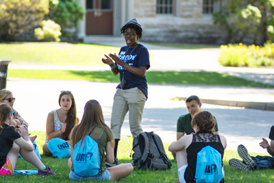student orientation leader talking to URI freshmen on the quad