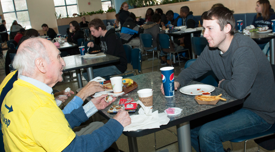 older adult sitting with a college student in the URI cafeteria
