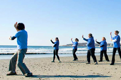 adults doing tai chi on a beach