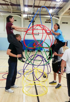 Kinesiology students building a tower with hula hoops