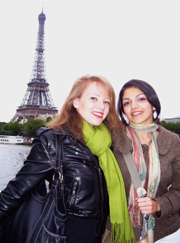 two smiling students in Paris with Eiffel Tower in background