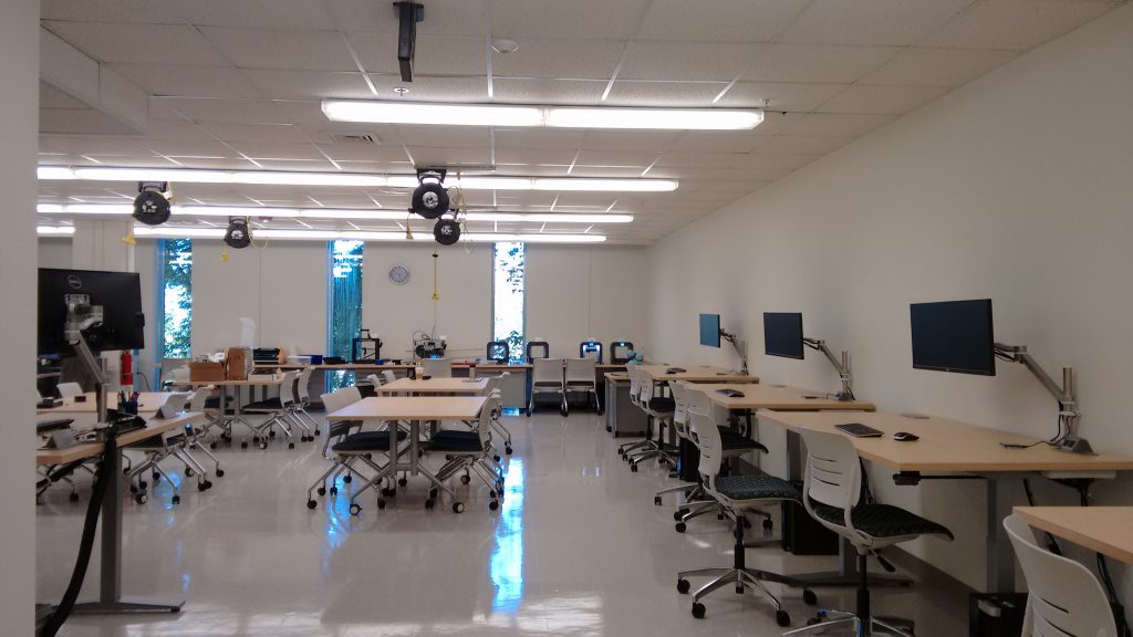 Workstations along right wall, 3D printers in back.