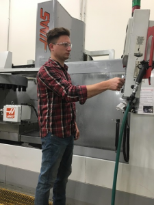 Pheland adjusting tool settings on a large vertical CNC machine.