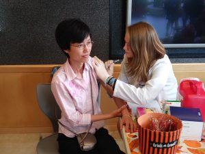 Fourth-year Pharmacy student Erin Connolly injects Xiaofeng Lin with the flu vaccine during a clinic in Avedisian Hall