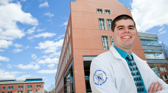 male pharmacy student smiling in front of new Pharmacy Building