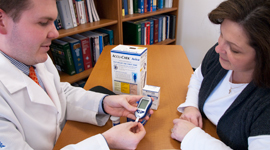 pharmacist demonstrating blood sugar testing to a client