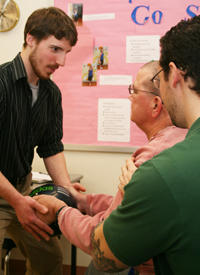 PT student working with a patient holding a ball