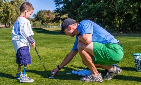 A student putting a golf ball on a tee for a child with prosthetic leg