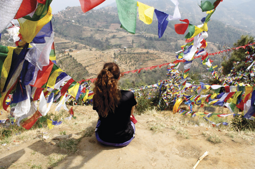 Natascha Shea '14 contemplates the enduring view from a mountain in Bharatpur during the Center for Nonviolence and Peace Studies 2013 Alternative Spring Break in Nepal. Prayer flags surround her, offering their blessings to the wind.