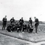Vintage photo showing a group of young men inspecting a section of grass.