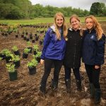 URI CELS students Becky Gumbrewicz, Sara Tucker and Sara Dotson pose as they prepare to plant a pollinator garden at URI