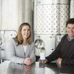 Cassandra Earle '04, Newport Vineyards marketing director, and co-owner John Nunes '88, at the tasting bar that faces the winery's massive fermentation tanks.